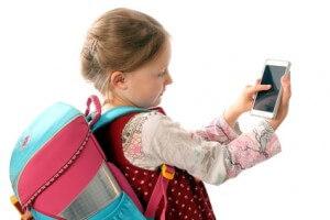 Schulmädchen tippt auf Smartphone